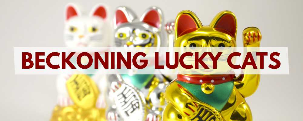Beckoning waving lucky cats in gold, silver and white